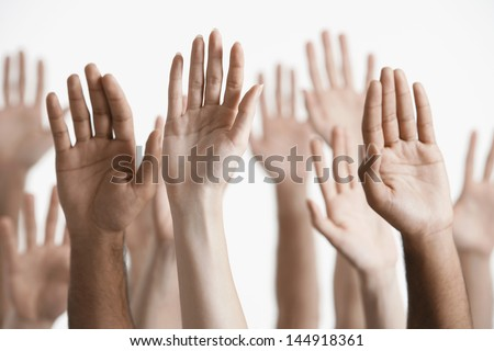 Closeup of multiethnic men and women raising hands against white background Royalty-Free Stock Photo #144918361