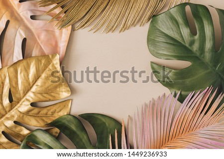 Creative layout made of colorful and golden tropical leaves and palms on beige background. Minimal summer exotic concept with copy space. Border arrangement background. #1449236933