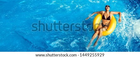 Summer vacation, Laughing young woman enjoying an aqua park with a yellow float on sparkling blue water in a pool with turbulence and copy space in an overhead panorama #1449255929