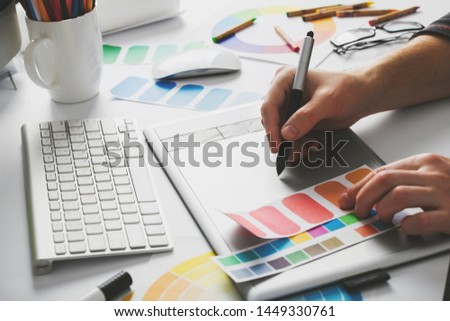 Young Handsome Graphic designer using graphics tablet to do his work at desk #1449330761