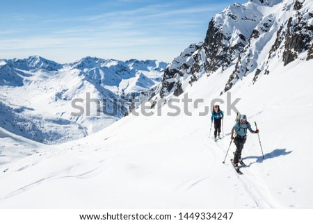 Two skiers skinning uphill on a hot sunny day in the Alaska backcountry of the Talkeetna Mountains. #1449334247