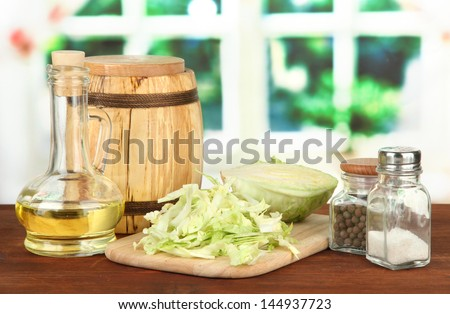 Green cabbage, oil, spices on cutting board, on bright background #144937723