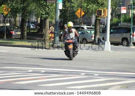 Electric Moped environmentally friendly Man riding on eastern parkway seen in crown heights section of Brooklyn on a sunny day july 12 2019 #1449496808