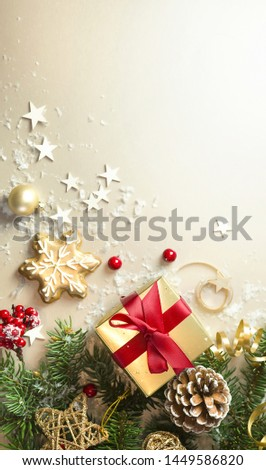 Christmas light gold background with beautiful Golden gift box with red ribbon, fir branches, cones, stars, Christmas cookies, top view, copy space #1449586820