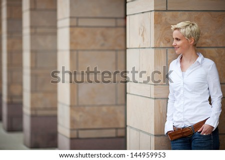 Pretty blonde with short cropped hair is leaning against wall #144959953