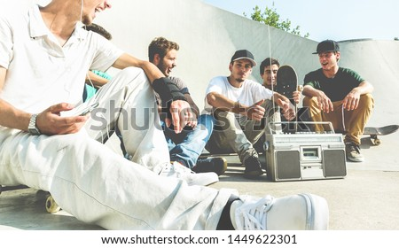 Young friends having fun at city skate park at sunset - Happy skaters laughing and listening music with vintage stereo - Extreme sport, friendship, youth, lifestyle concept - Focus on right man face #1449622301