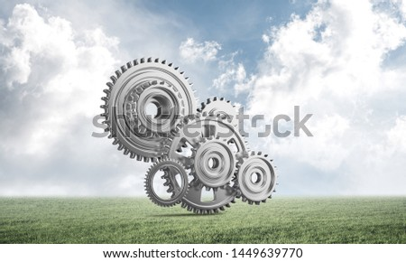 Abstract mechanism with cogwheels on green meadow. Construction and manufacturing. Mechanical technology machine engineering. Nature landscape with green grass and blue sky. Mixed media with 3D object #1449639770
