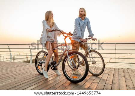 attractive happy couple of friends traveling in summer on bicycles, man and woman with blond hair boho hipster style fashion having fun together, walking by the sea in resort city #1449653774