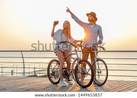 attractive happy couple traveling in summer on bicycles, man and woman with blond hair boho hipster style fashion having fun together, taking photos sightseeing #1449653837