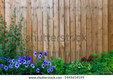 Wooden fence in a frame of green and purple flowers Royalty-Free Stock Photo #1449654599