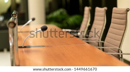 Isolated view of a microphone in a meeting room on a table with blurred chairs - close-up with selective focus, very little depth of field and much copyspace Royalty-Free Stock Photo #1449661670