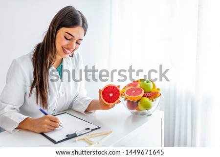Smiling nutritionist in her office, she is showing healthy vegetables and fruits, healthcare and diet concept. Female nutritionist with fruits working at her desk.  #1449671645
