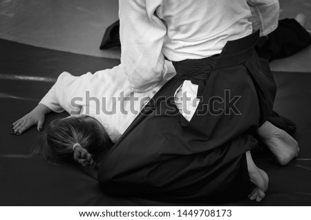 Black and white image of aikido. Athlete girls involved in martial art of Aikido. The traditional form of clothing in Aikido. Royalty-Free Stock Photo #1449708173