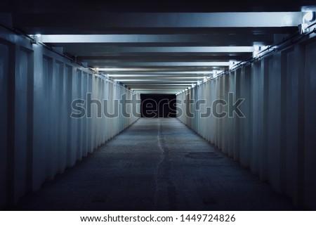Underground pedestrian crossing. A long concrete tunnel with lanterns in the city underground. Underpass. underground passage #1449724826