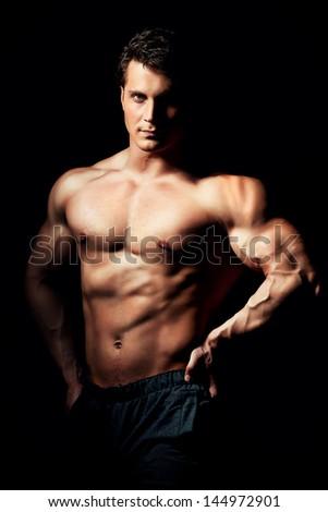 Portrait of a handsome muscular bodybuilder posing over black background. #144972901
