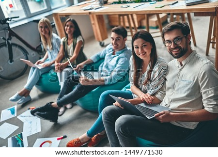 Group of young business people are working together in modern office. Creative people with laptop, tablet, smart phone, notebook. Successful hipster team in coworking. Freelancers. #1449771530