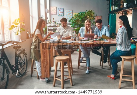 Group of young business people are working together in modern office. Creative people with laptop, tablet, smart phone, notebook. Successful hipster team in coworking. Freelancers. #1449771539