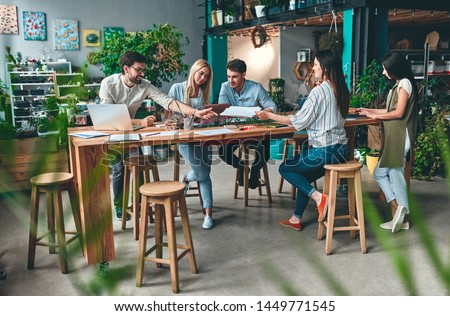 Group of young business people are working together in modern office. Creative people with laptop, tablet, smart phone, notebook. Successful hipster team in coworking. Freelancers. Royalty-Free Stock Photo #1449771545