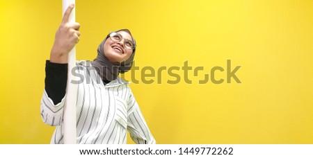 Kuala Lumpur, Malaysia - July 2019: Stylish hijab women with beautiful smile look happy. Yellow background.  #1449772262