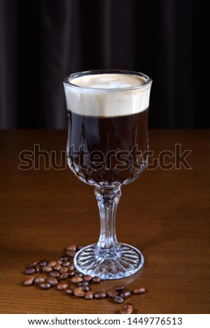 Irish coffee in a glass cup on a wooden table. Dark background. #1449776513