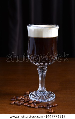 Irish coffee in a glass cup on a wooden table. Dark background. #1449776519