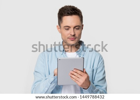 Handsome man standing scrolling and typing on electronic tablet device. Happy male holding gadget using popular application, typing message on screen. Photoshoot at studio isolated on gray background #1449788432