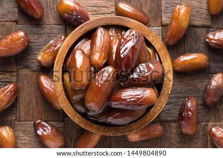 dried date fruit in bowl on wooden table background. Royalty-Free Stock Photo #1449804890