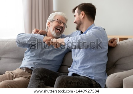 Happy old senior father and son fists bumping, celebrating success or greeting each other, mature aged dad and millennial man having fun together, sitting on couch at home, enjoying weekend #1449927584