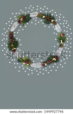 Christmas and winter wreath with snow covered spruce fir, mistletoe, acorns, cedar leaves, ivy and loose snowflakes on grey background with copy space. #1449927746
