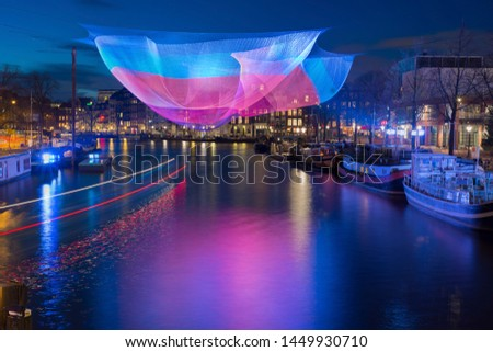 Amsterdam in winter time with beautiful lights and light trails of passing canal bus during Amsterdam Light Festival. #1449930710