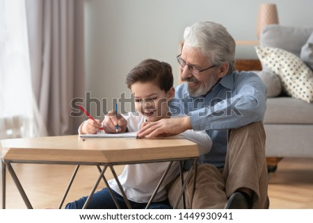 Happy grandfather playing with little grandson, drawing colored pencils, smiling granddad and cute preschool grandchild sitting on warm floor together, having fun at home, underfloor heating #1449930941