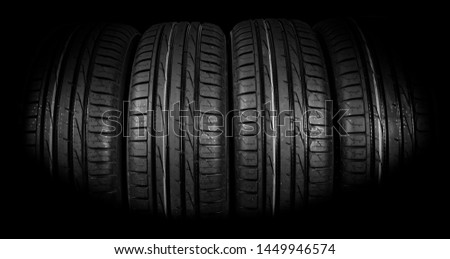 Studio shot of a set of summer car tires on black background. Tire stack background. Car tyre protector close up. Black rubber tire. Brand new car tires. Close up black tyre profile. Car tire in a row #1449946574