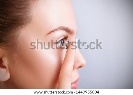 Side view on young woman wearing green contact lenses. Over blue background. Royalty-Free Stock Photo #1449955004