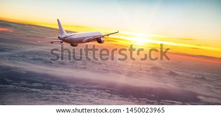 Commercial airplane jetliner flying above dramatic clouds in beautiful sunset light. Travel concept. #1450023965