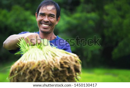 Smiling of happy agriculture farmer,rice growing season started in the rainy season every year in Thailand.farmers, rice farmers, happy farmers-image. #1450130417