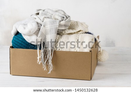 Winter clothes in a cardboard box. Seasonal clothing for shipping or donation.