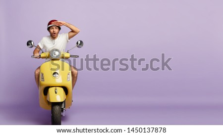 Surprised motorcyclist notices something strange on road, keeps hand near forehead, focused into distance, poses on fast yellow motorbike, wears protective helmet, enjoys riding. Copy space. #1450137878