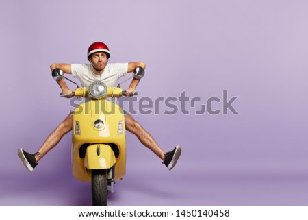 Funny young man with fasten motorbike helmet, poses on fast bike, wears white t shirt and sneakers, poses against purple background with empty space. People, transportation and riding concept #1450140458