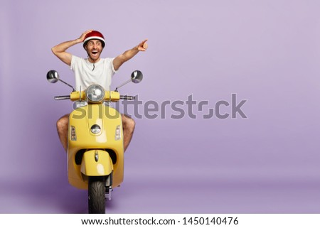 Surprised active man rides fast motorbike, points into distance, stares with shock, notices something incredible, wears protective helmet, isolated on purple background with blank copy space #1450140476