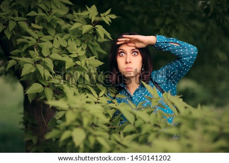 Curious Jealous Woman Spying from Bushes. Funny undercover girl stalking outdoors in surveillance mode  #1450141202