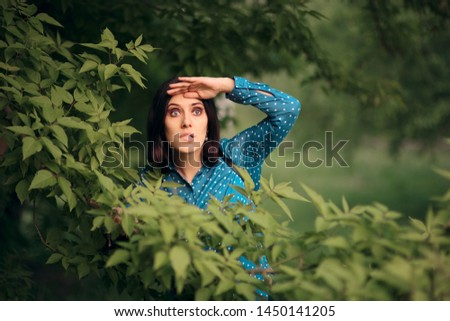 Curious Jealous Woman Spying from Bushes. Funny undercover girl stalking outdoors in surveillance mode  #1450141205