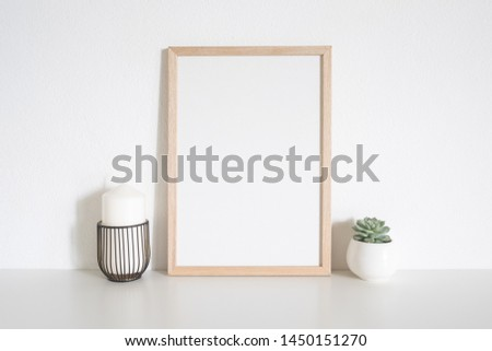 Brown wooden frame photo and white candle on table at home. Scandinavian style #1450151270
