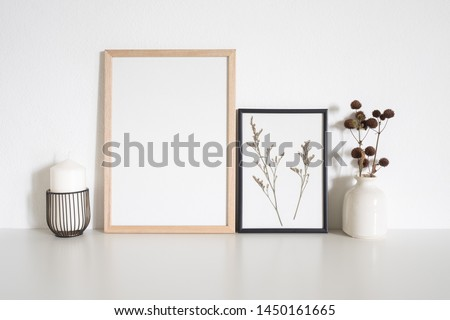Mock up frame poster with candle and dried flowers on table in white room. Interior scandinavian style #1450161665