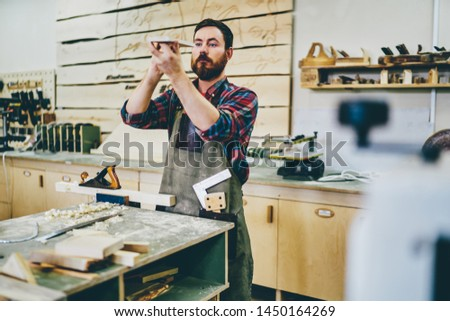 Bearded carpenter enjoying hobby working process at his workstation of manufacturing, side view of skilled self employed artisan in apron checking element for handmade construction of wooden plank #1450164269