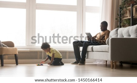 Biracial little boy play toy cars racing on floor, young african American dad sit on couch using tablet, black father and preschooler son have fun relaxing in living room, spend weekend at home #1450166414