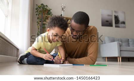 Loving young african American dad lying on floor with little son drawing in album at home together, black father spend time learning with preschooler boy child paint picture with pencil on paper #1450166423