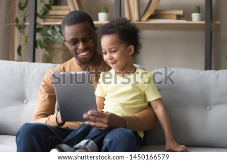 Excited loving african American dad hold tablet sit on couch with cute preschooler son watch cartoon together, smiling happy black dad and small boy kid relax on sofa at home play game on pad