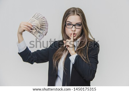 Satisfied, excited young business woman is showing a pile of money, isolated on white background. Girl has a lot of money. Serious girl makes Shh.. gesture. Nobody should know about her money.