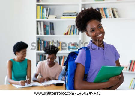African american female young adult with students and teacher at classroom of university #1450249433