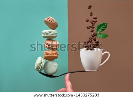 Conceptual image of perfect balance between two issues. Macarons and cup of coffee on spoon balanced on human finger.  #1450275203